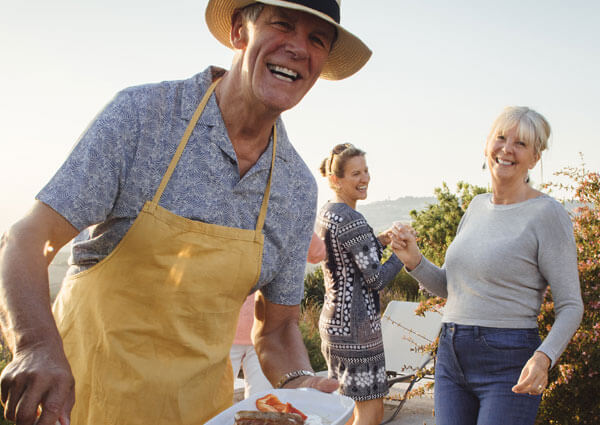 Older gentleman in a hat enjoying bbq with his family